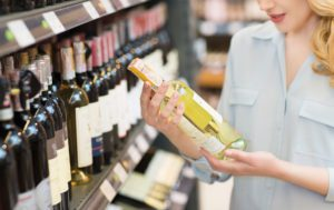 Liquor Store Insurance - Header - Woman Picking Out A Bottle Of Wine In A Liqour Store